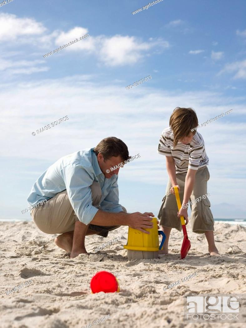 Stock Photo: Father and son making sandcastles.