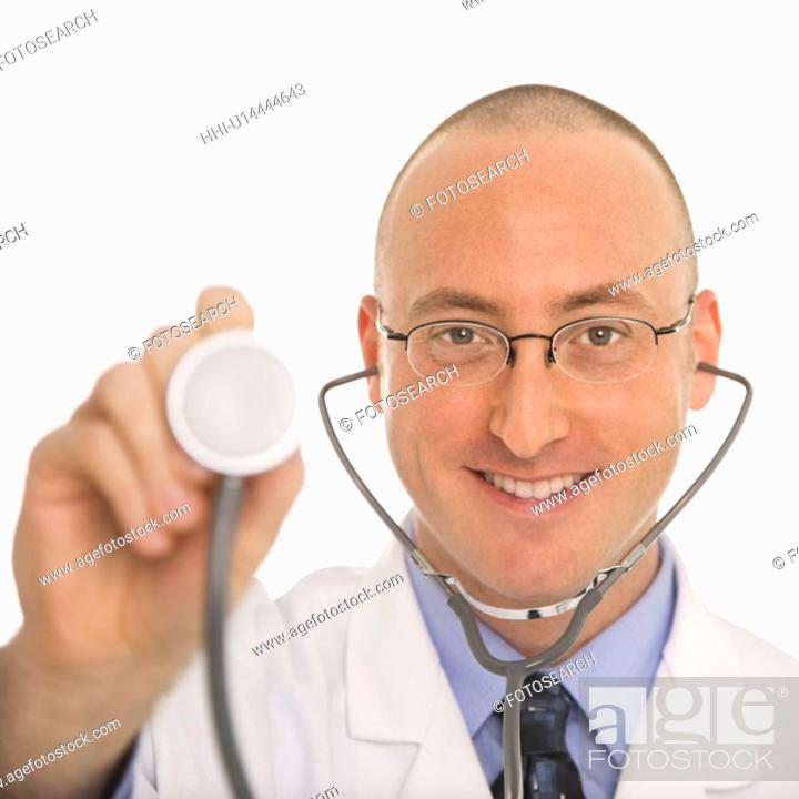 Stock Photo: Caucasian mid adult male physician holding up end of stethescope.