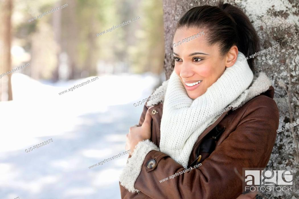 Stock Photo: Smiling woman leaning against tree trunk in snow.