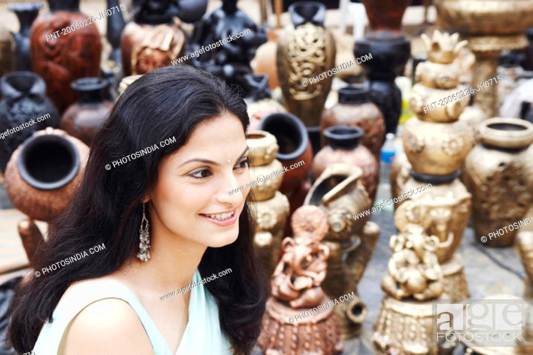 Stock Photo: Side profile of a young woman smiling in a pottery store.