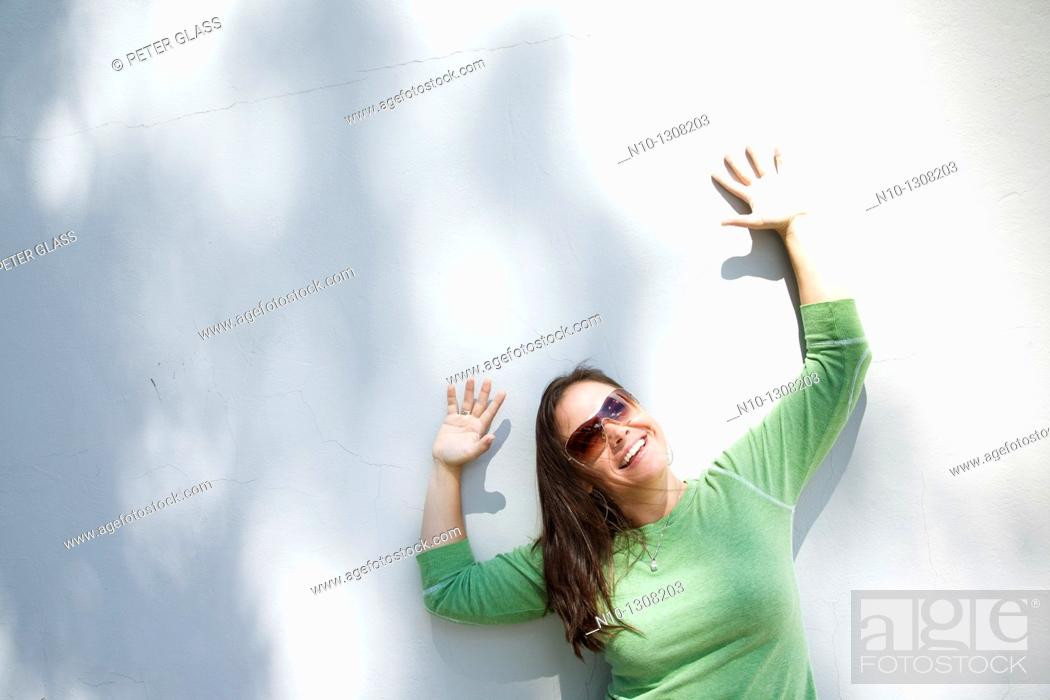 Stock Photo: Young woman in front of a wall.