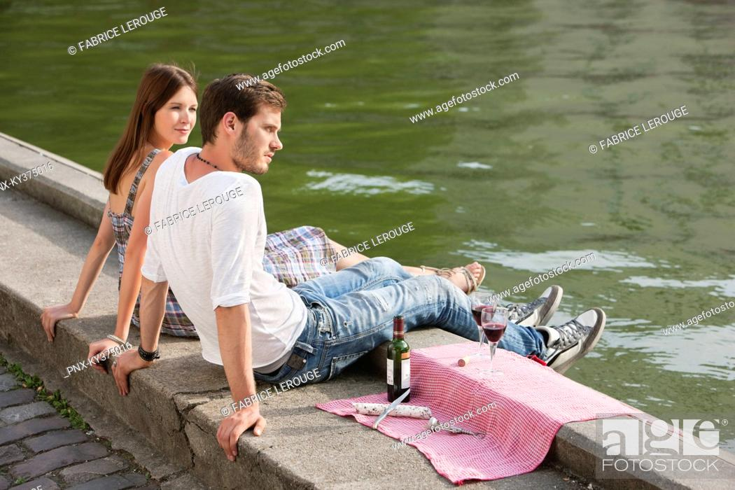Stock Photo: Couple sitting at the ledge of a canal, Paris, Ile-de-France, France.