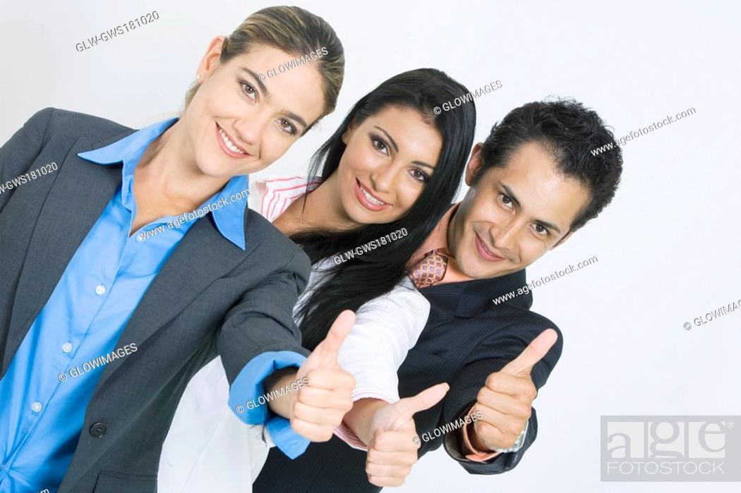 Stock Photo: Portrait of two businesswomen and a businessman standing in a row and making a thumbs up sign.