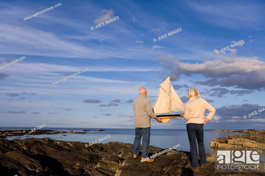 Stock Photo: Senior couple with model boat on rocks by sea, rear view.