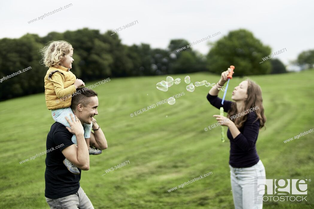 Stock Photo: Family blowing bubbles in park. Munich, Germany.