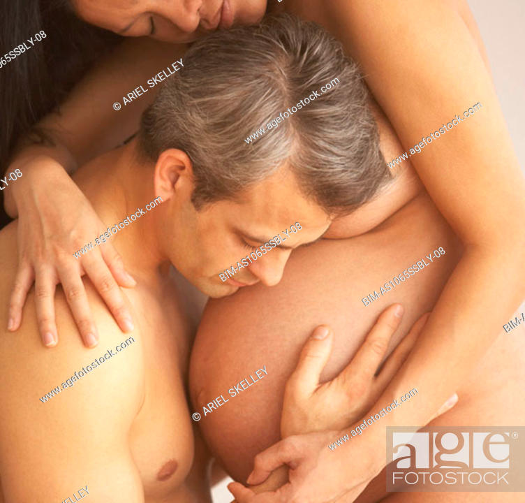 Stock Photo: Man embracing his nude pregnant wife.