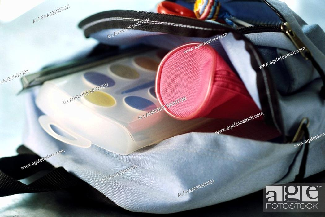 Stock Photo: Backpack containing pencil case and watercolor paints.