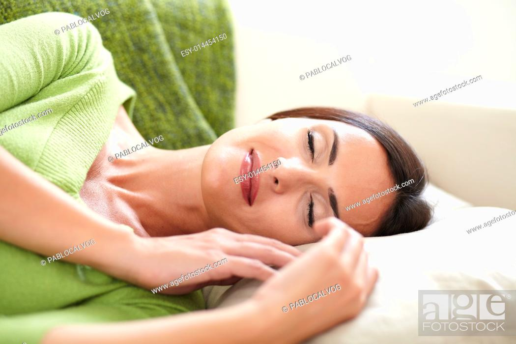 Stock Photo: Carefree woman lying on her back and resting indoors with her eyes closed.