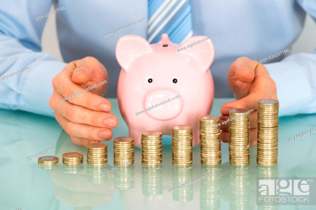 Stock Photo: Businessman Covering Piggy Bank With Stacked Coins At Desk.