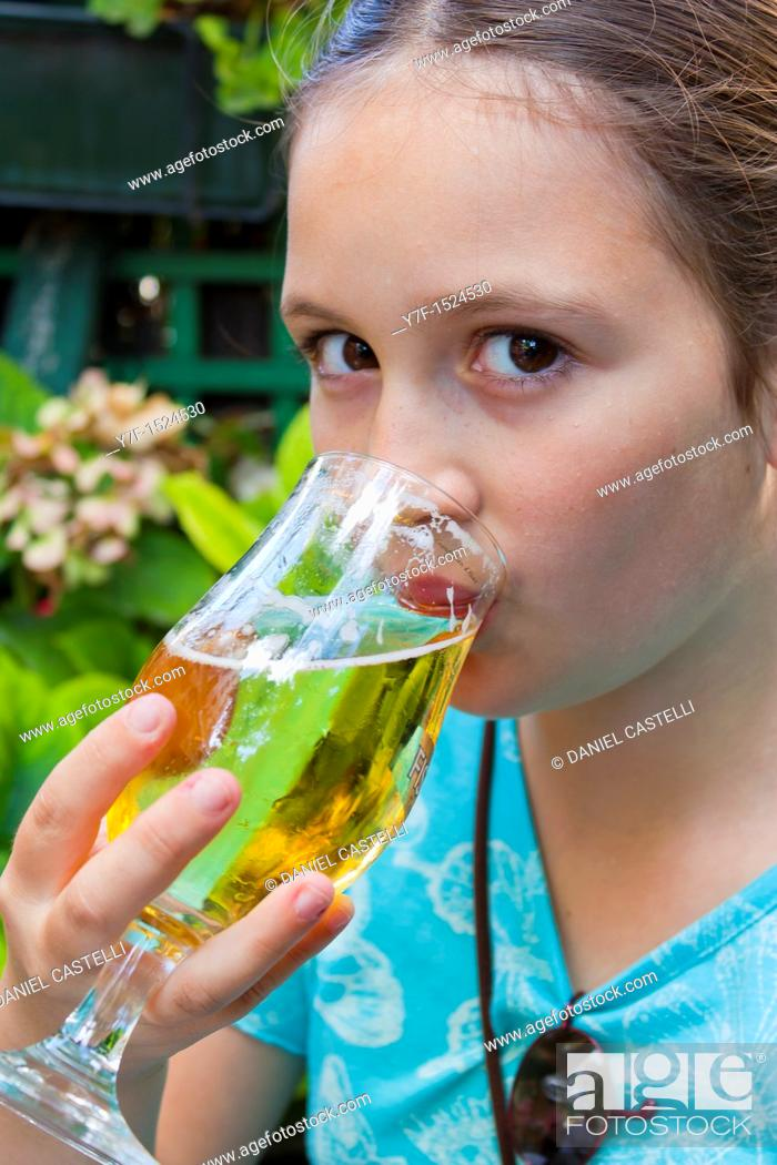 Photo de stock: Brown eyed teenager drinking a glass of beer in a french café, Paris, France.