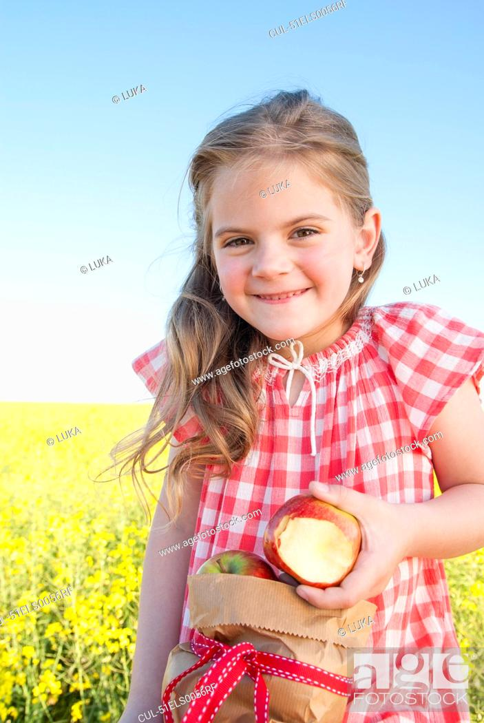 Stock Photo: Girl eating sack of apples outdoors.