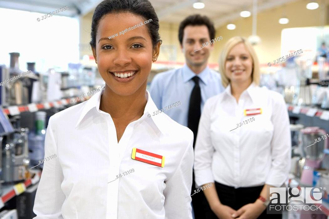 Stock Photo: Young saleswoman by colleagues in shop, smiling, portrait.