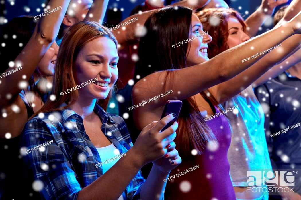 Stock Photo: party, holidays, celebration, nightlife and people concept - smiling young woman with smartphone texting message at concert in club and snow effect.