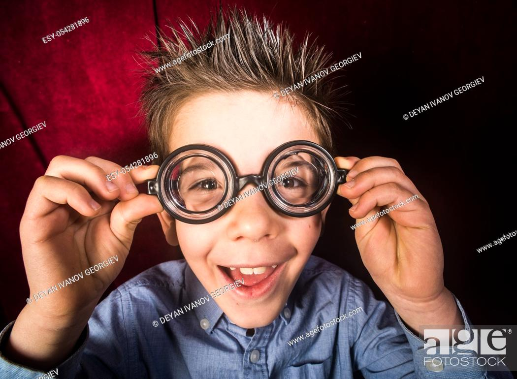 Stock Photo: Smiled child with big glasses. Red curtain background.