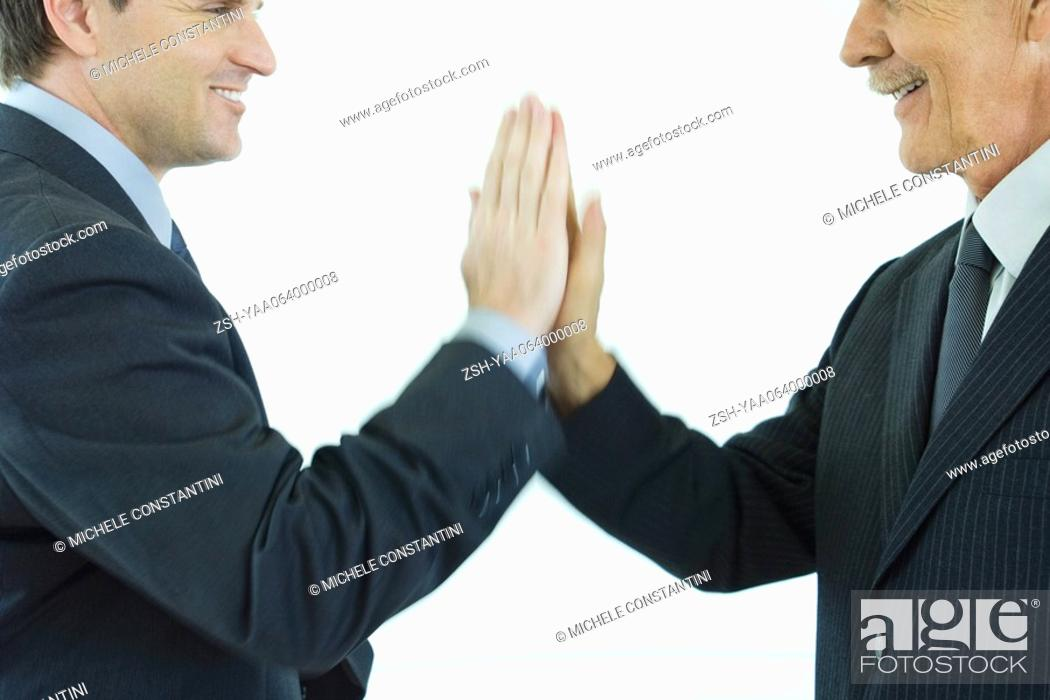 Stock Photo: Two businessmen giving each other a high-five, cropped side view.