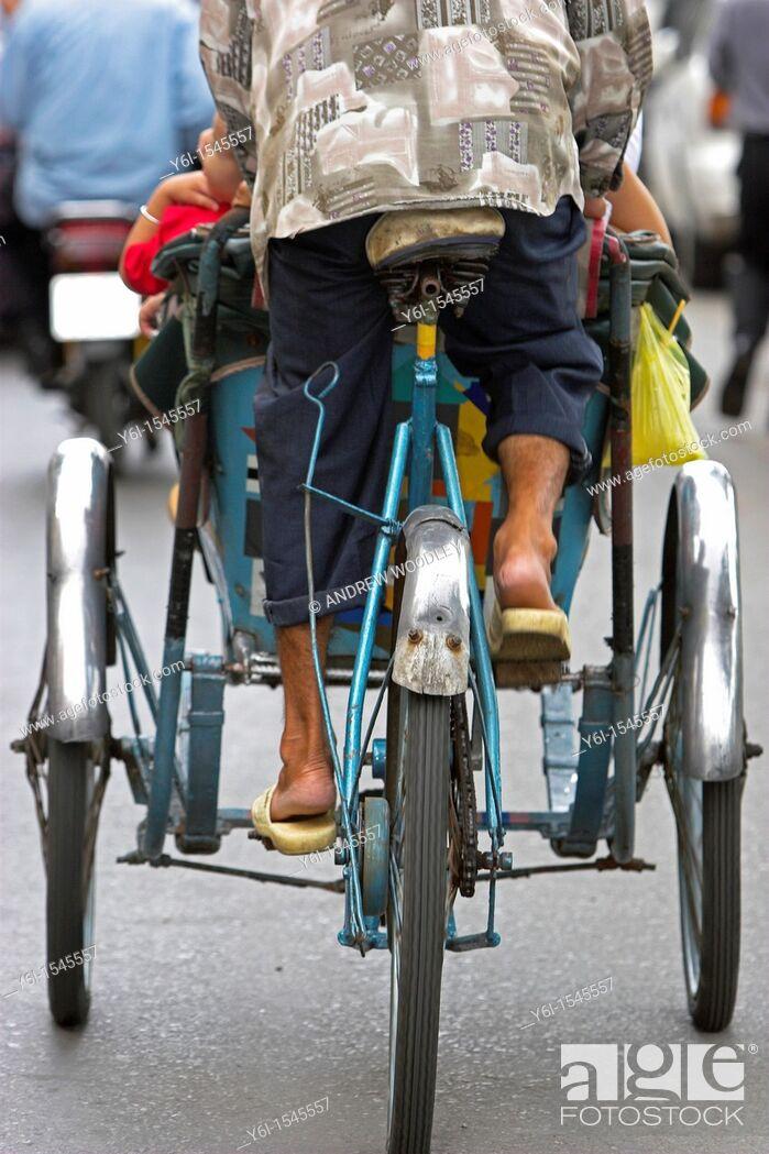 Stock Photo: Rear view of cyclo rickshaw and driver Ho Chi Minh City Vietnam.