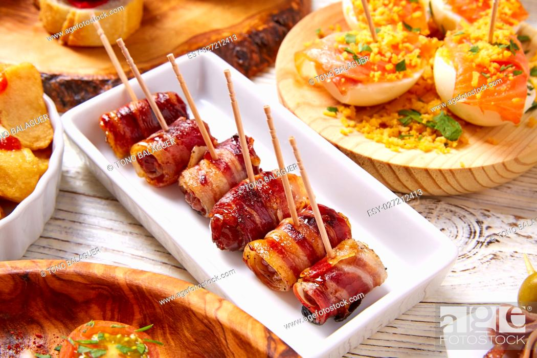 Imagen: Tapas mix and pinchos food from Spain recipes also pintxos on a white wood board.