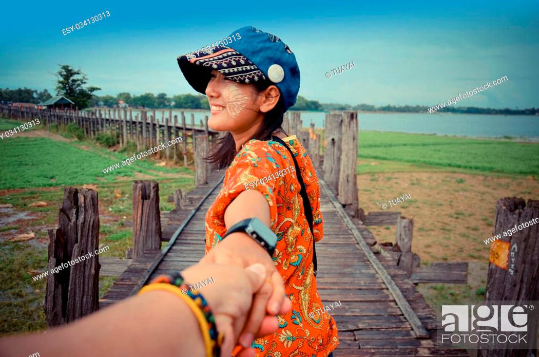 Stock Photo: Thai woman lead someone by the hand and hold on the walkway.