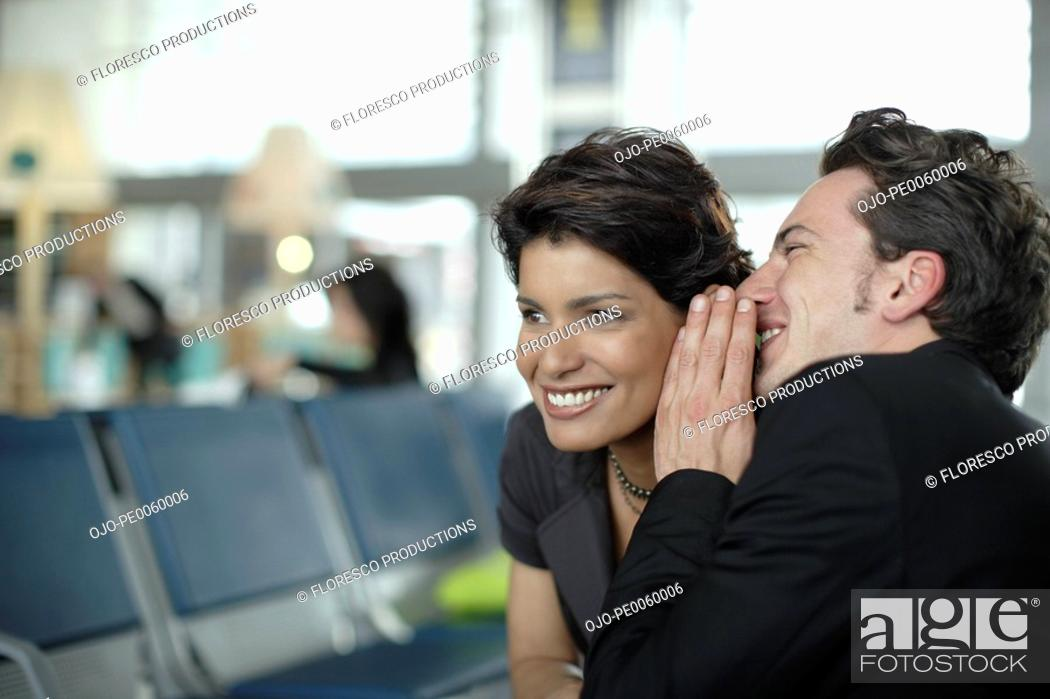 Stock Photo: Man in airport whispering in woman's ear.