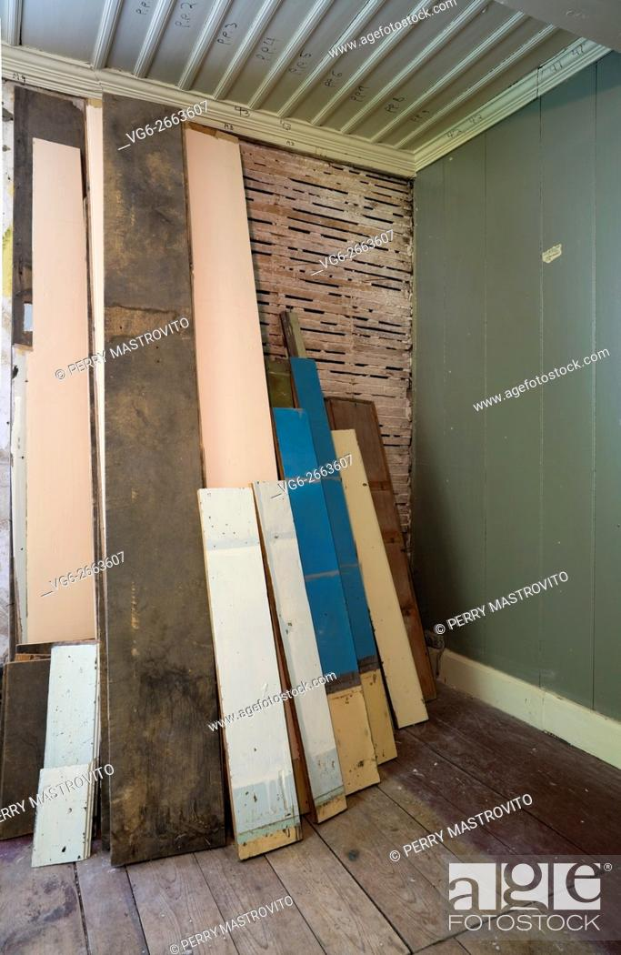 Stock Photo: Stacked wooden planks and partially demolished plaster and wooden lattice wall in a empty room inside an old 1800s cottage style home, Quebec, Canada.