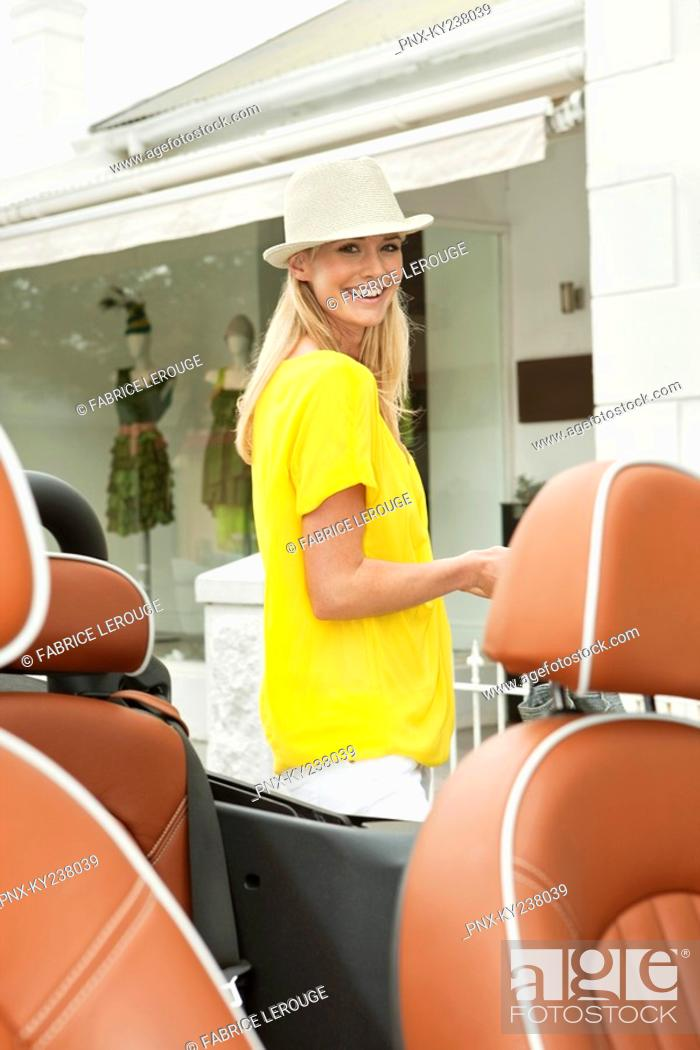Stock Photo: Woman smiling near a car after shopping.