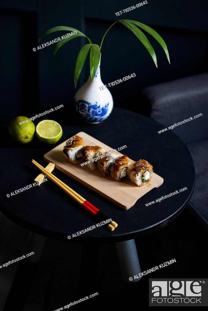 Stock Photo: Sushi on table with chopsticks, vase and lime.