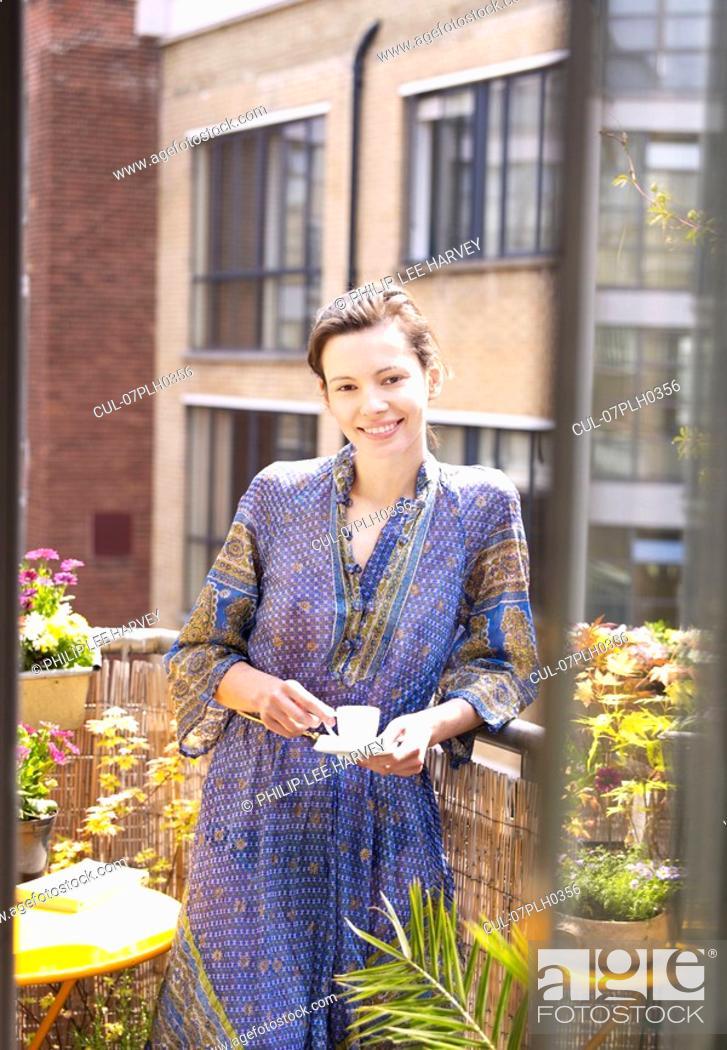 Stock Photo: Woman on balcony with espresso.
