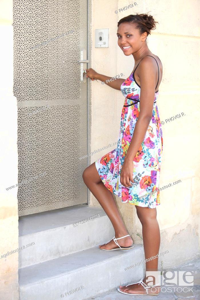 Photo de stock: Young woman unlocking her front door.