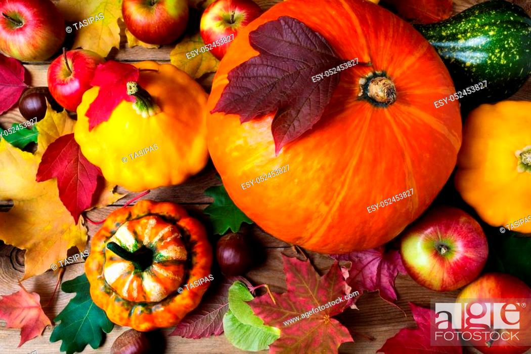 Stock Photo: Red apples, pumpkins and yellow gourd with colorful fall leaves, top view. Thanksgiving or fall greeting background.