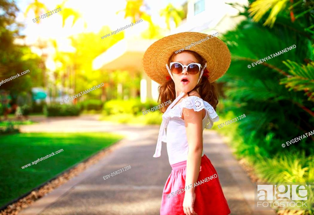 Stock Photo: a funny surprised child girl in summer hat and glasses.