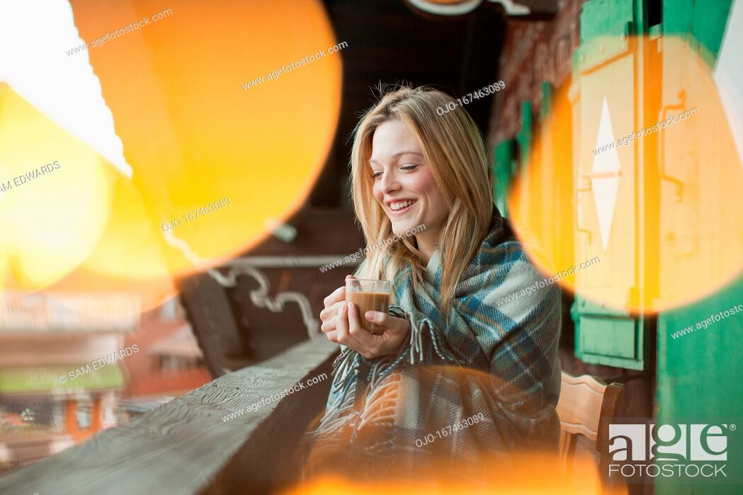 Stock Photo: Smiling woman wrapped in a blanket and drinking coffee on cabin porch.