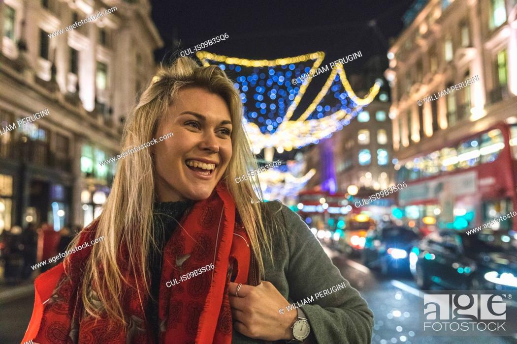 Stock Photo: Young woman walking along illuminated street, smiling.
