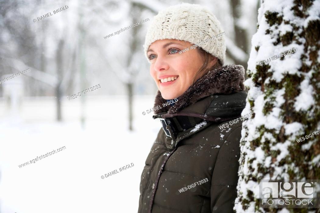 Photo de stock: Portrait of smiling woman leaning at tree trunk in winter.
