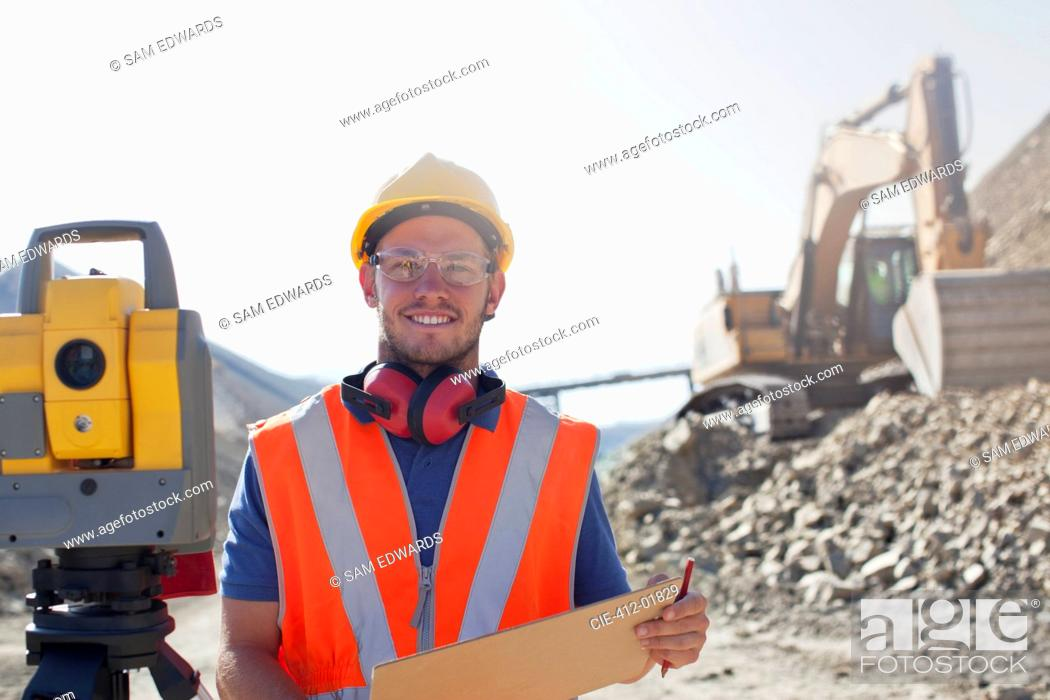 Stock Photo: Worker using leveling equipment in quarry.