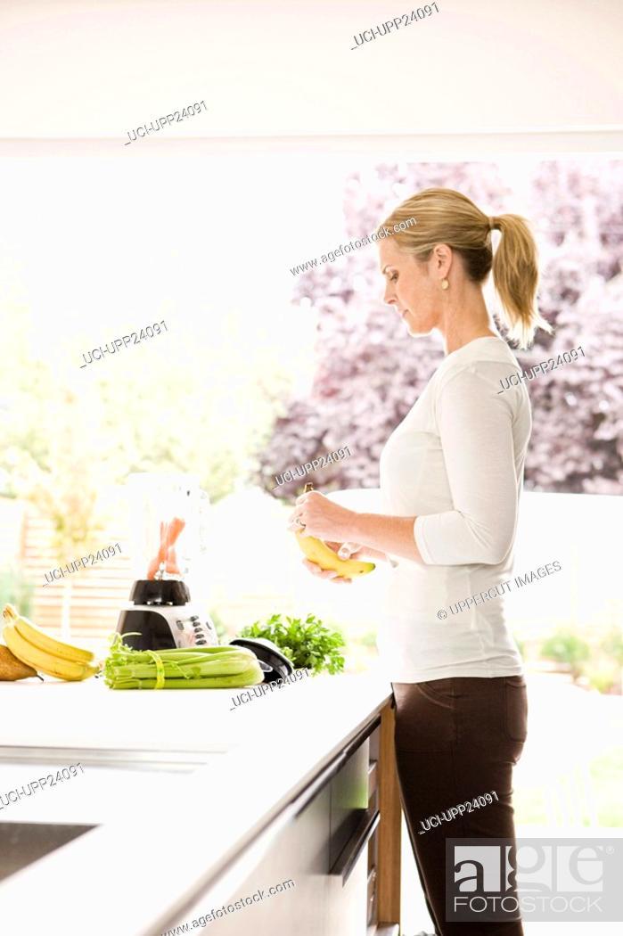 Stock Photo: Woman preparing health shake in kitchen.