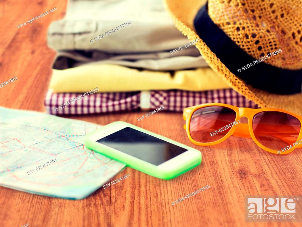 Stock Photo: travel, summer vacation, tourism and objects concept - close up of folded clothes, smartphone and touristic map on wooden floor.