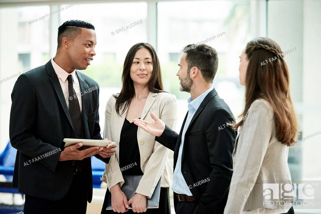 Stock Photo: Business people standing and discussing in the hotel lobby.