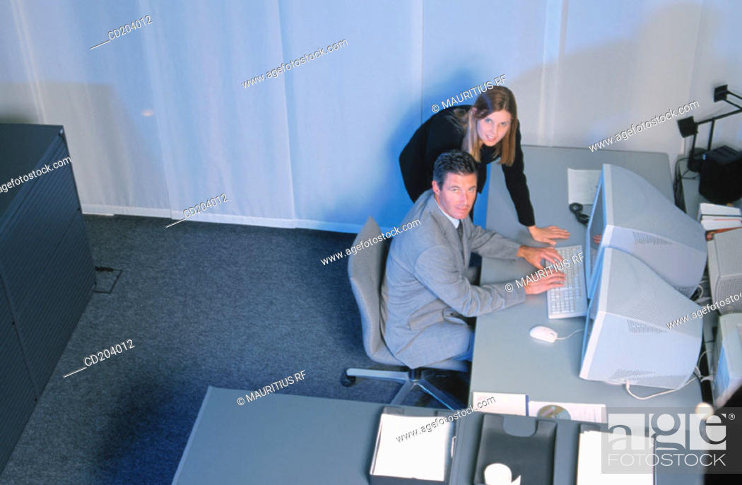 Stock Photo: Two businesspeople in front of computer, businessman typing, both looking at camera.