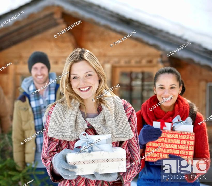 Stock Photo: Portrait of smiling friends holding Christmas gifts in front of cabin.