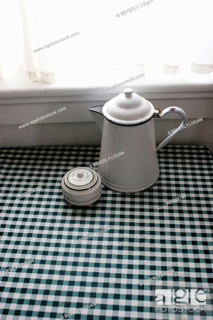 Stock Photo: Coffee pot and sugar bowl on a table in front of a window.