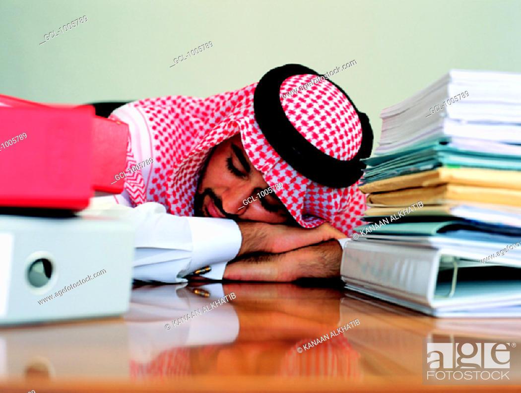 Stock Photo: Arab businessman sleeping at his desk.
