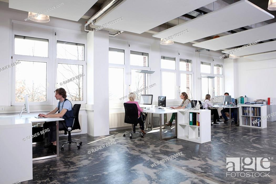 Stock Photo: Germany, Bavaria, Munich, Men and women working on computer in office.