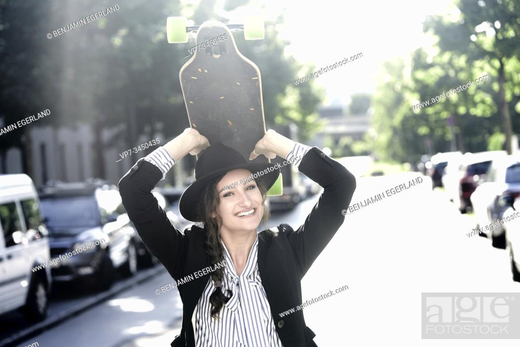 Stock Photo: Woman wearing hat, holding skateboard over her head. Munich, Germany.