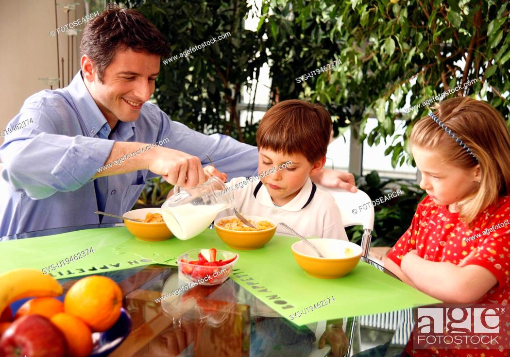 Stock Photo: Father and children eating breakfast.