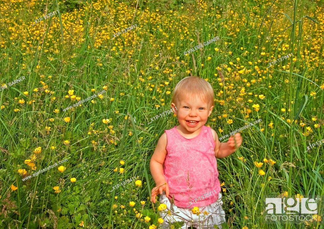 Stock Photo: This cute Caucasian eighteen month old toddler girl is smiling and happy in long grass and buttercups  She's wearing a pink shirt and has blue eyes and blond.