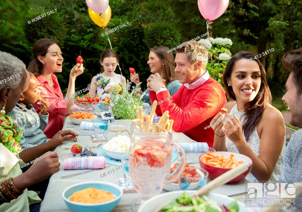 Stock Photo: Family and friends enjoying birthday garden party at patio table.