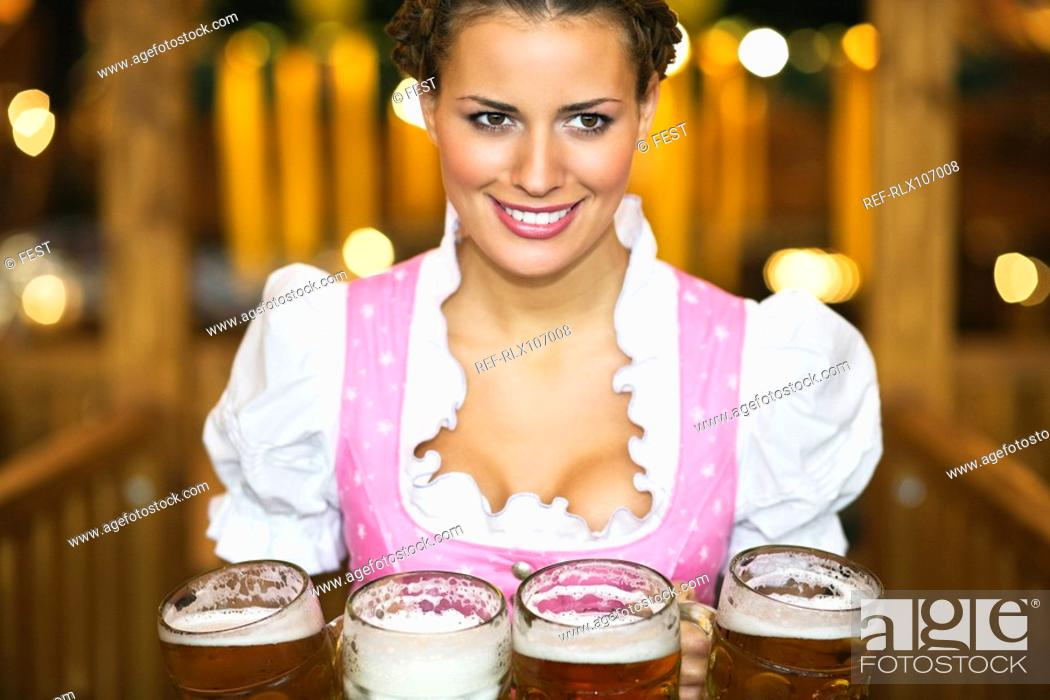 Stock Photo: Waitress holding 4 Mass beer jugs at Oktoberfest, Munich, Germany.