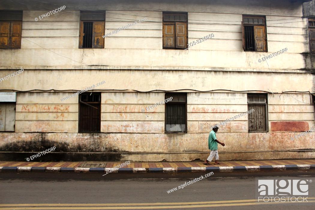 Stock Photo: PUNE, MAHARASHTRA, INDIA, October 2018, Man walking past an old house.