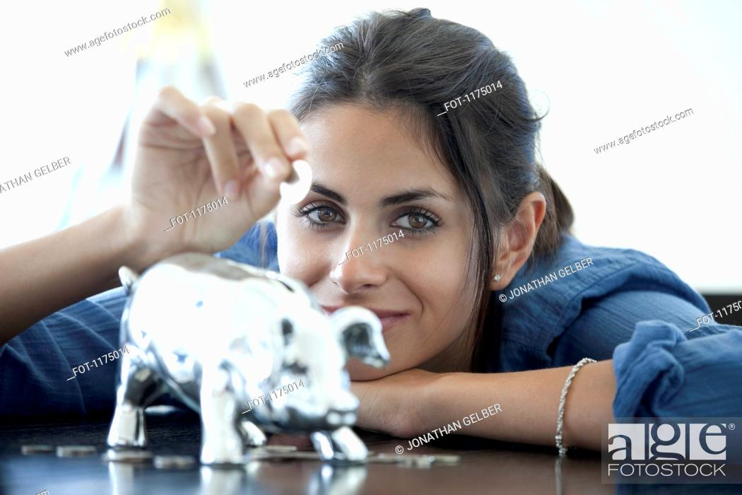 Stock Photo: Woman putting coin into piggy bank.