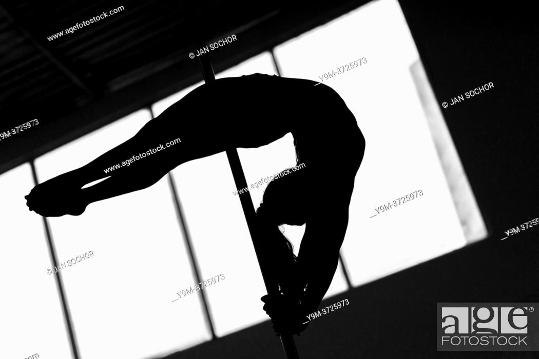 Stock Photo: A young Colombian pole dancer demontrates her gymnastics skills during a pole dance training session in a gym in Bogotá, Colombia, 24 October 2019.
